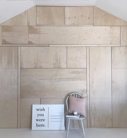 Plywood wall with print and chair in front