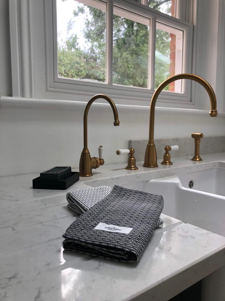 Marble kitchen counterrop with brass taps, black soap and grey washcloths