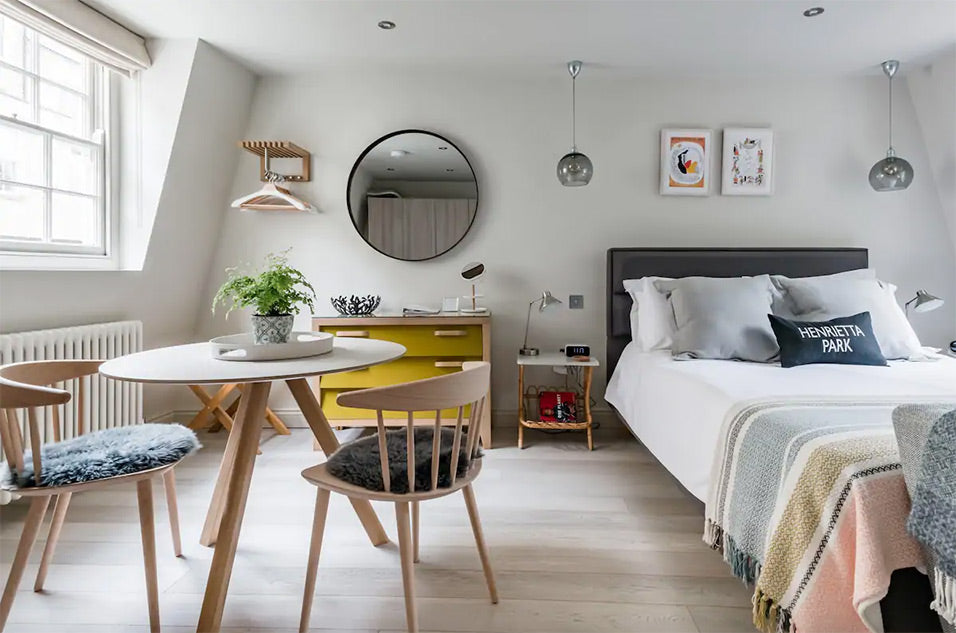 Bed and dining table in modern studio apartment