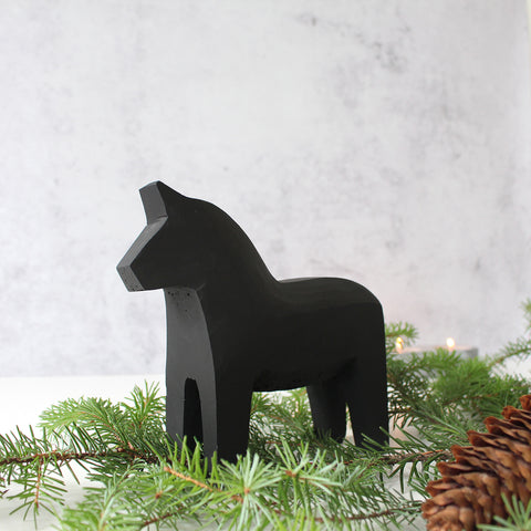 Black dala horse and fir branch