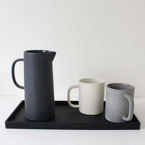 Ceramic jug (black) and mugs (white, grey) on a black rubber tray