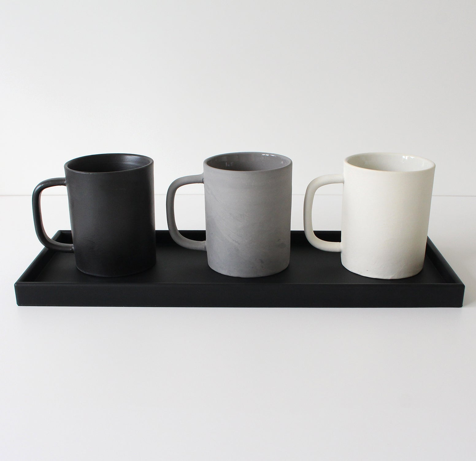 Black rubber tray with 3 ceramic mugs, one black, one grey, one white
