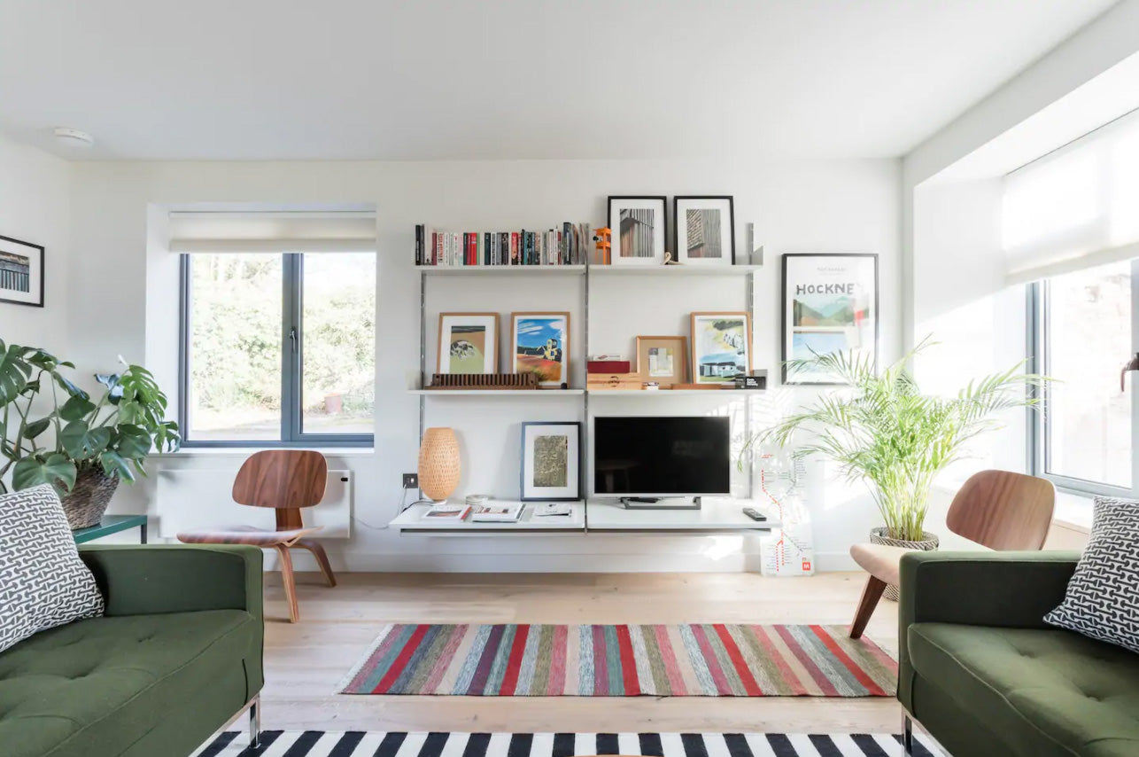 Living room with modern shelving, green sofas and stripey rugs
