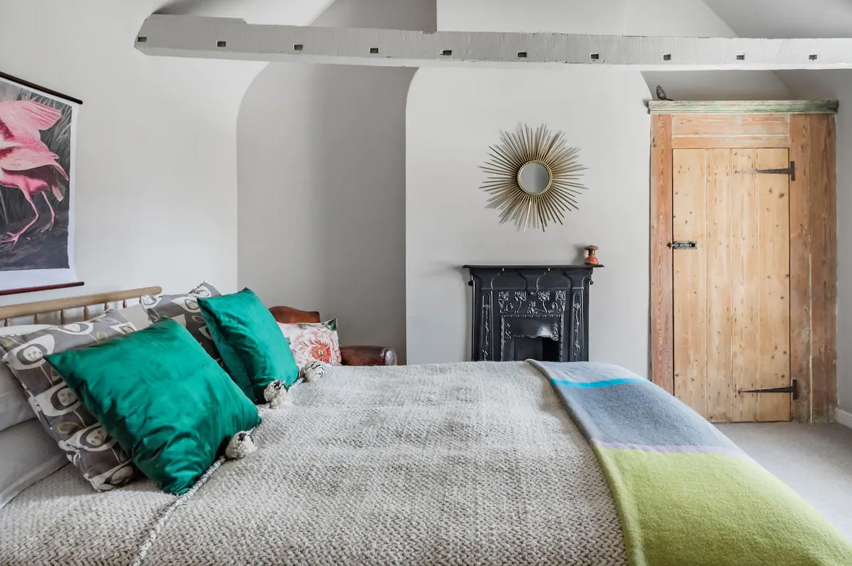 Bedroom with beams and fireplace. Cozy bed with cushions