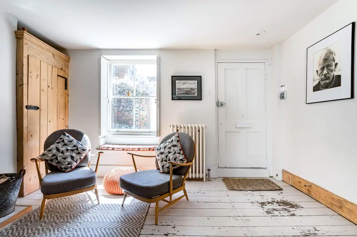 Townhouse lounge with white painted floorboards and grey furniture