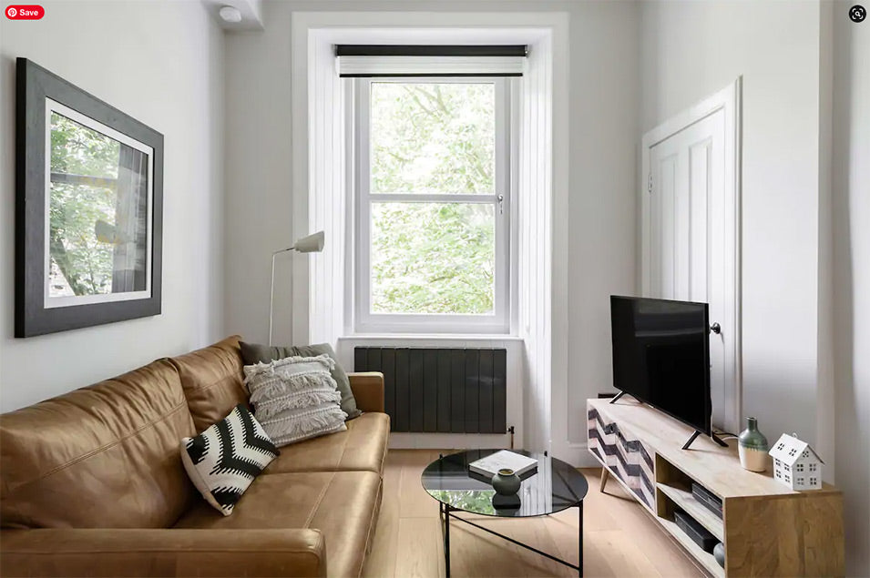 Narrow living room with brown leather sofa and wooden furniture