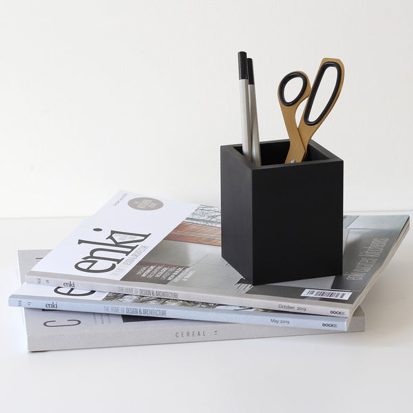 Black rubber stationery pot with scissors and pencils, on top of a small pile of design magazines