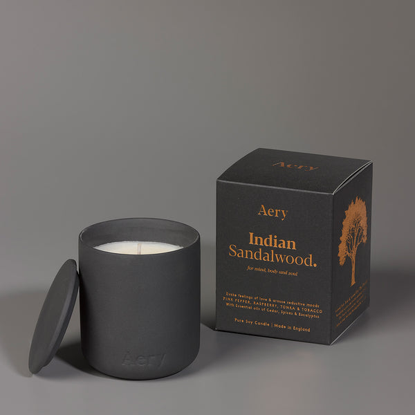 Scented candle in black ceramic pot next to packaging (black with copper foil)