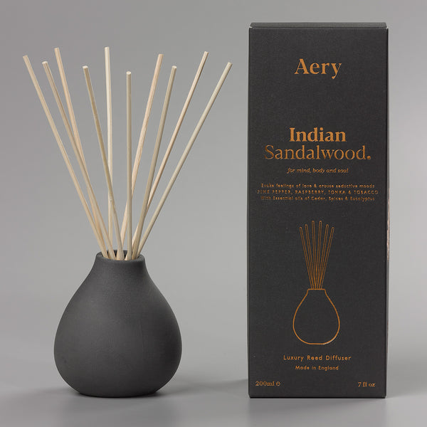Reed diffuser in ceramic tear-drop vase next to packaging box (black with copper foil)