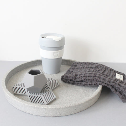 Collection of grey items: concrete tray, reusable coffee cup, wash cloth, ceramic pot and silicone coaster