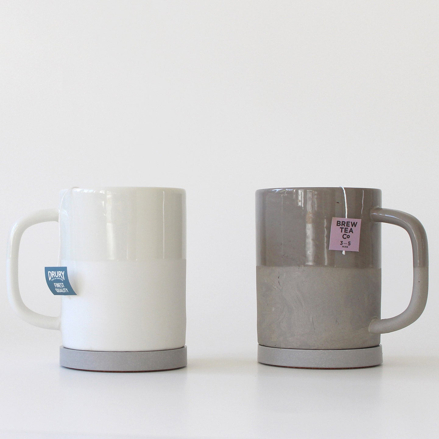 Two ceramic mugs, one white, one grey, with tea bags. Sat on grey jesmonite coasters