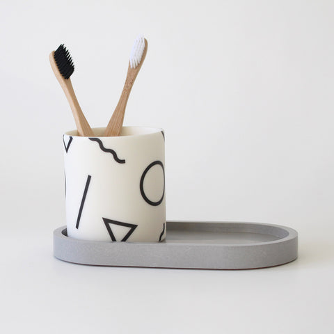 Black and white ceramic pot holding 2 bamboo toothbrushes. The pot is sitting on a grey oval jesmonite tray.