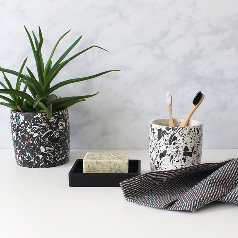 Styled bathroom lifestyle shot: black terrazzo plant pot, white terrazzo toothbrush pot, rubber soap dish with bar soap and grey wash cloth