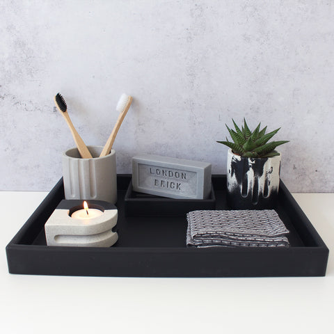 Styled bathroom tray all in monochrome, including toothbrushes in a holder, tealight candle holder, pot with succulent, bar soap on a soap dish and a wash cloth.