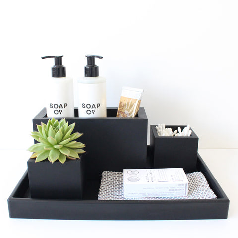 Bathroom tray with a collection of black rubber pots, toiletries and a succulent plant