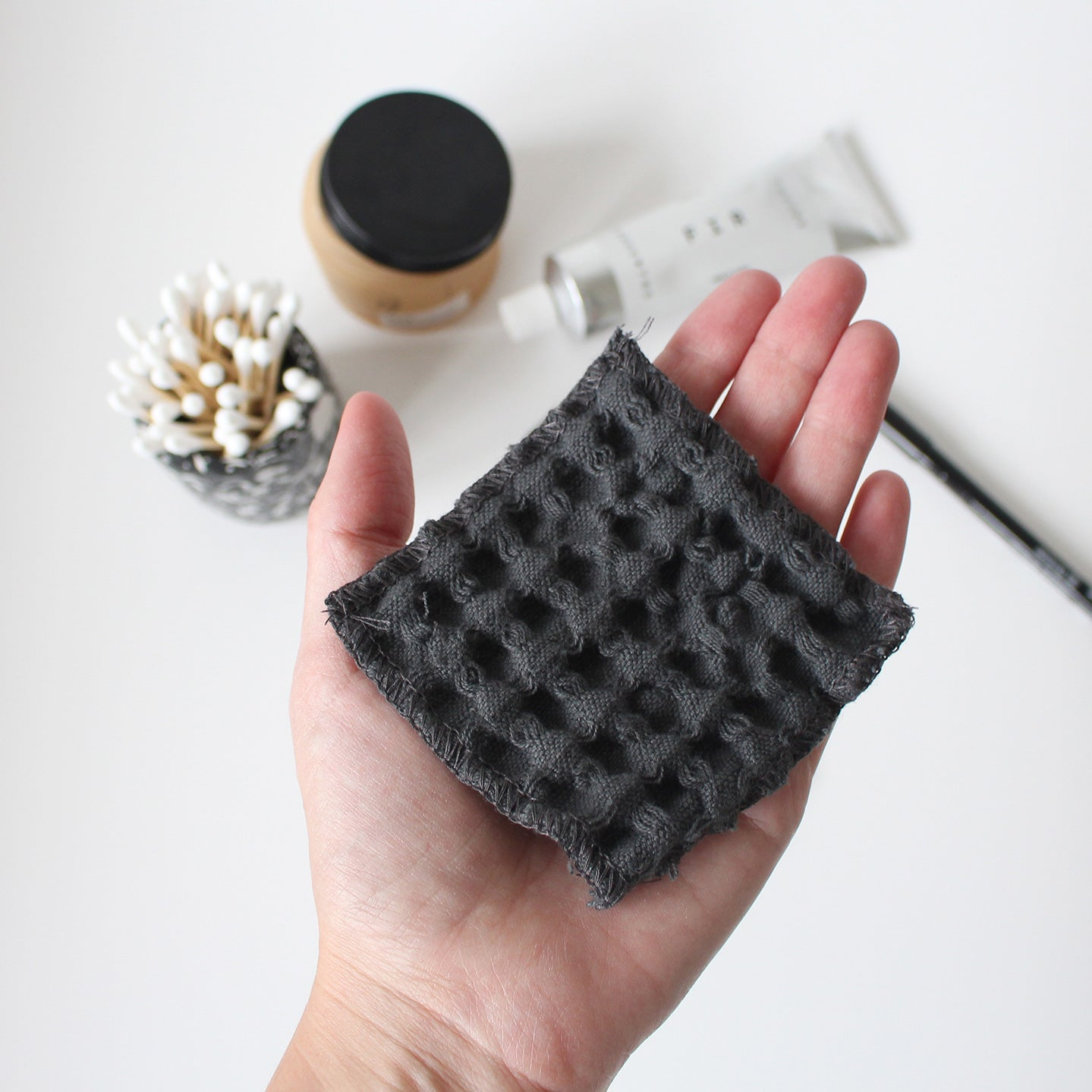 Grey waffle make-up pad held in a hand. In background - q-tips, moisturiser, hand cream
