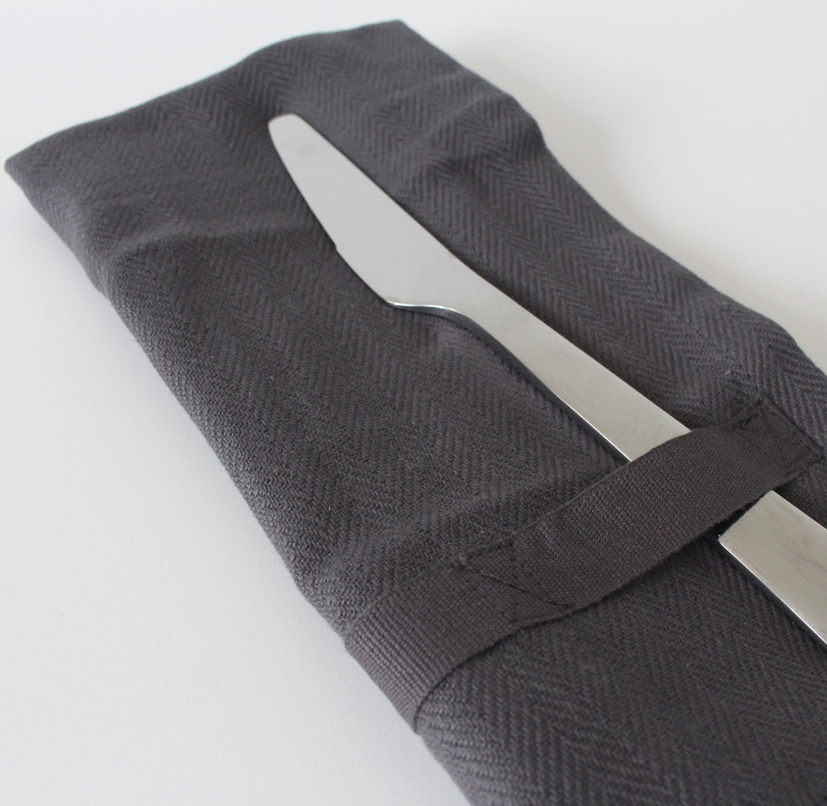 Dark grey napkin, folded with a table knife tucked through the strap