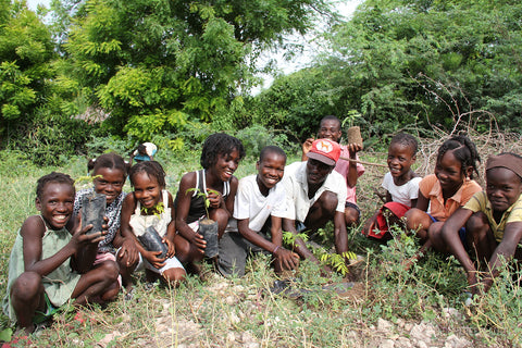 Group of smiling children with tree saplings