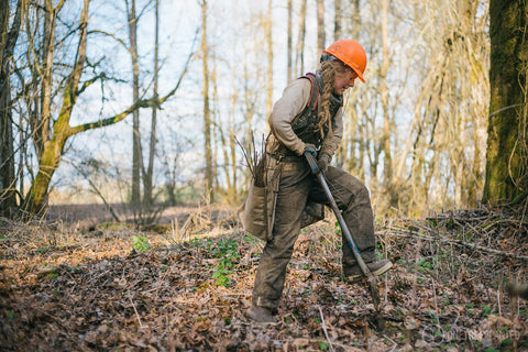 Woman in hard hat planting trees in a forest