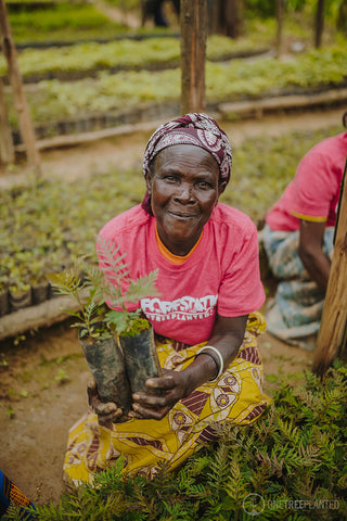 Smiling woman holding sapling trees for planting