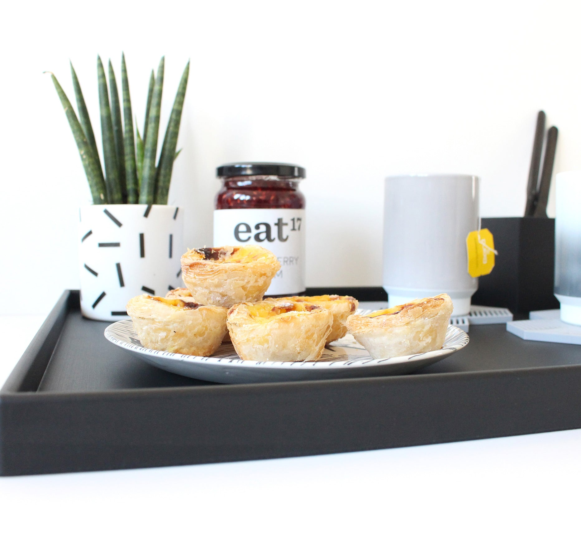 Serving tray with potted plant, jam, custard tarts, tea cups, cutlery etc.