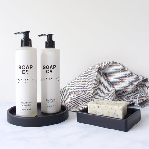 Collection of monochrome toiletries - hand wash, hand lotion, bar soap, wash cloth, soap dish and tray