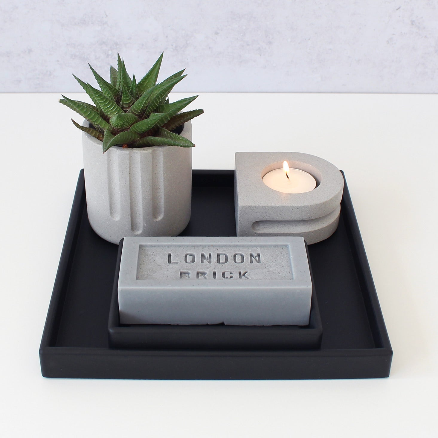 Bathroom tray. Black rubber tray with black rubber soap dish, grey bar soap, lit tealight candle in grey holder, succulent plant in grey pot