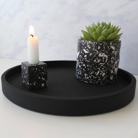 Black terrazzo plant pot and candlestick on a black concrete tray