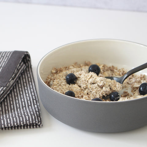 Cereal in grey ceramic bowl with black spoon and grey napkin