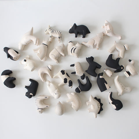 Large collection of wooden animals, all lying down