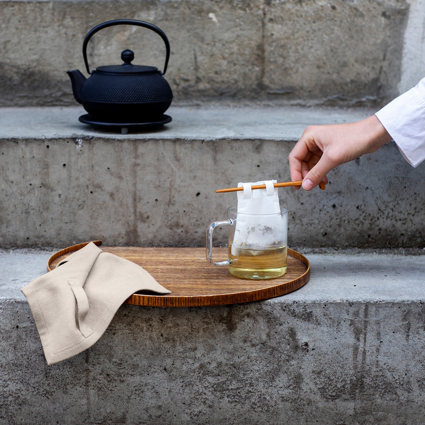 Concrete steps with tea making equipment: black traditional kettle, wooden tray with cotton cloth and tea in a glass mug