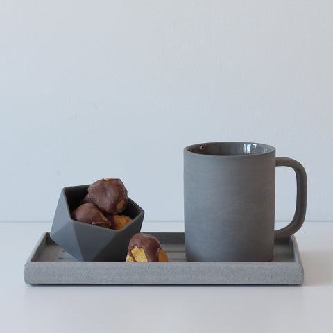 Grey tray with grey ceramic mug and grey geometric pot filled with chocolate-coated honeycomb