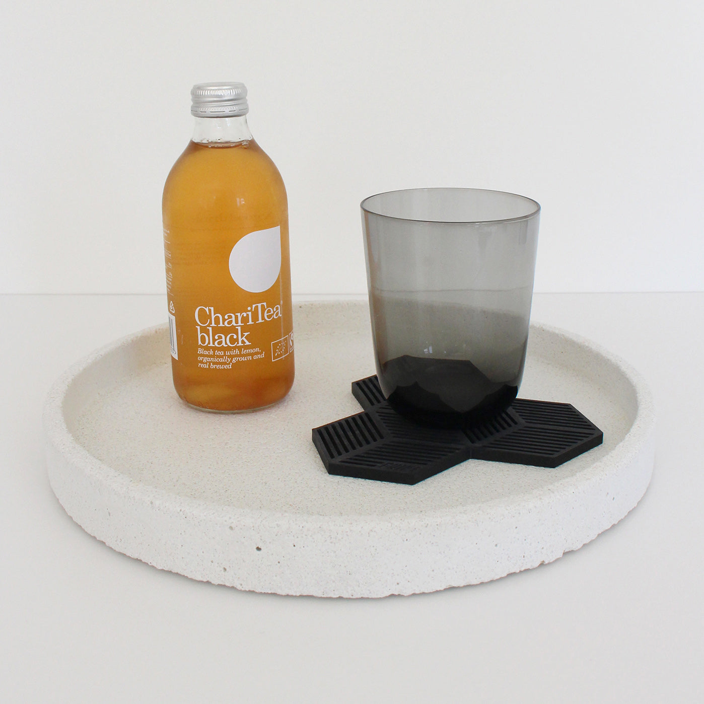 Bottle of ice tea and a glass on a white concrete tray