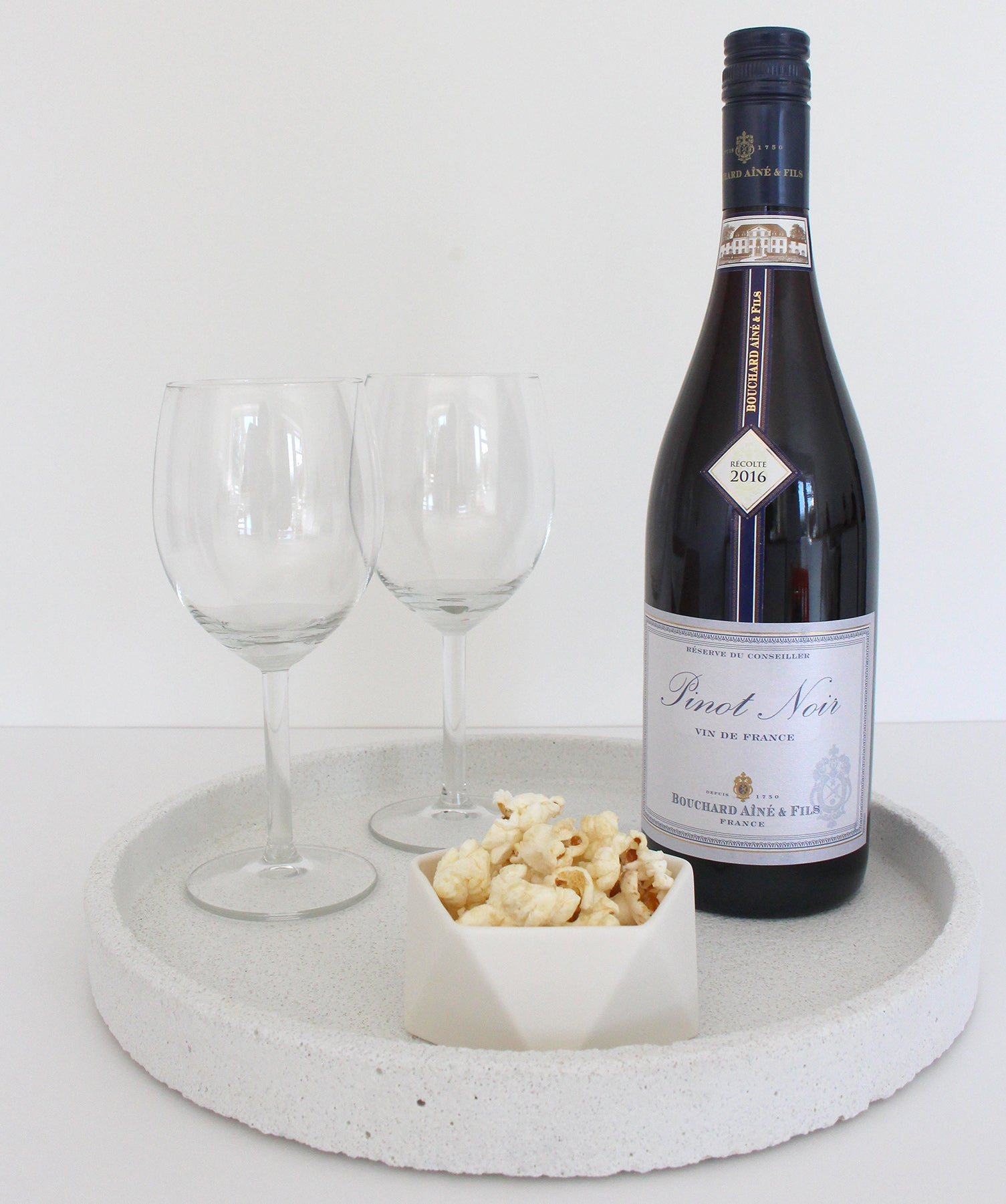 Bottle of wine, 2 wine glasses and a ceramic pot of popcorn on a white concrete tray