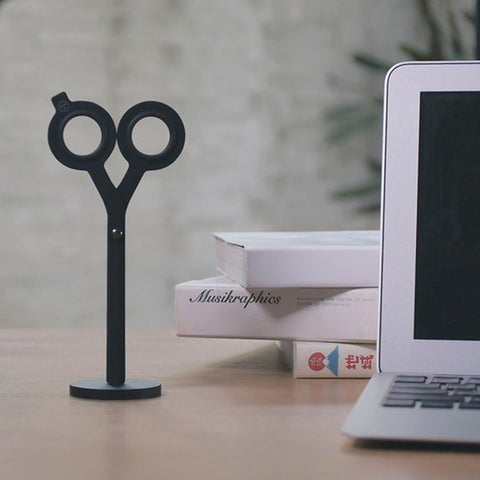 HMM Scissors on magnetic base next to laptop and pile of books