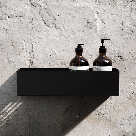 Black metal bathroom shelf with Aesop toiletries displayed
