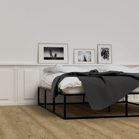 Black metal bed frame, made up with white and grey bedding. Wooden floor, monochrome prints on wall