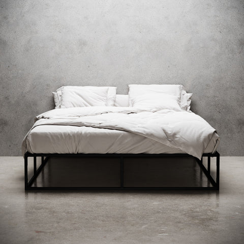 Black metal bed frame, made up with white linens