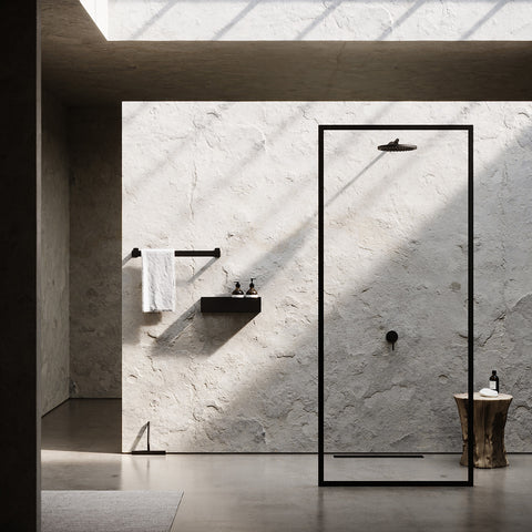 Minimal bathroom with rough stone walls and black fittings