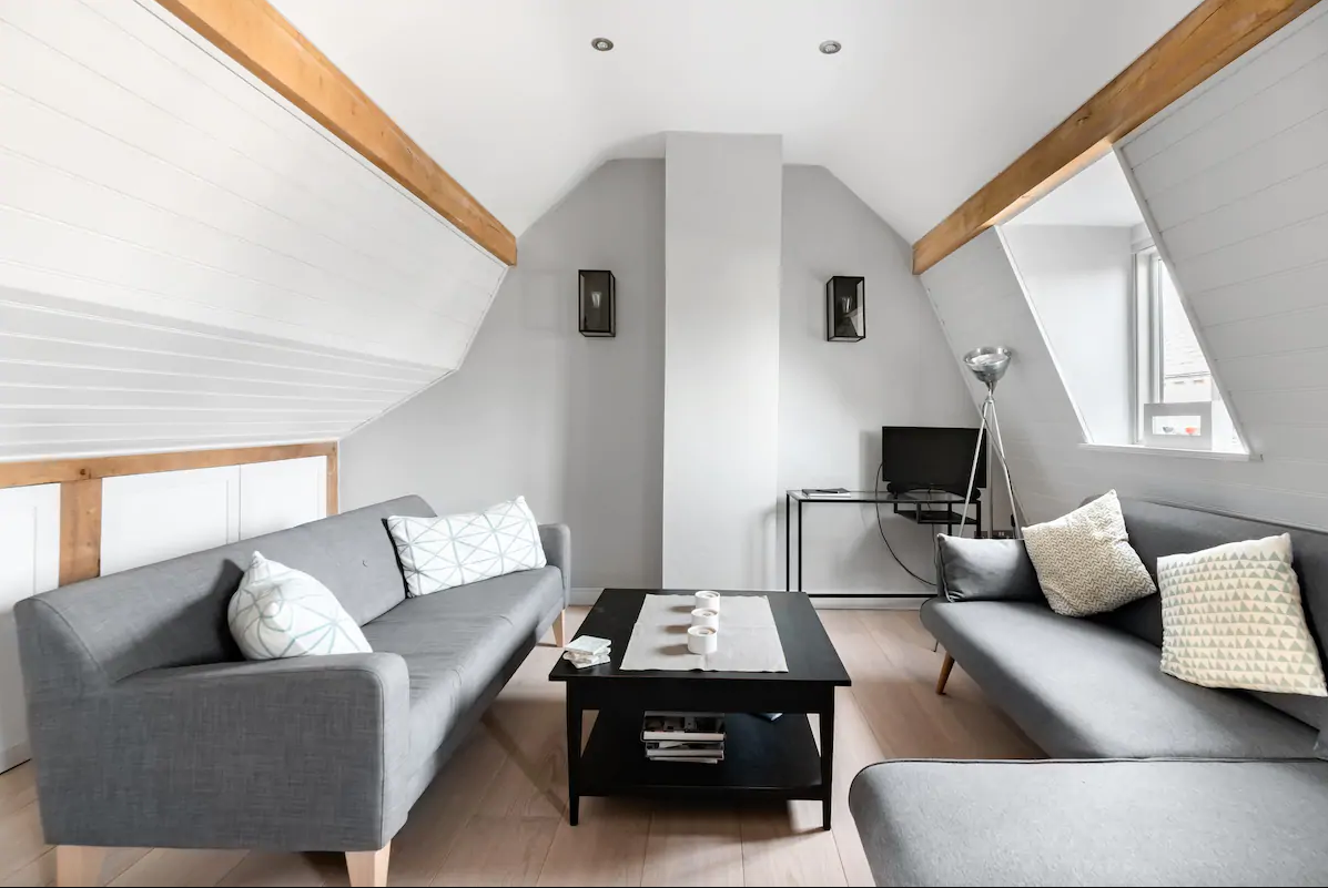 Modern living room in the eaves. Grey sofas and walls