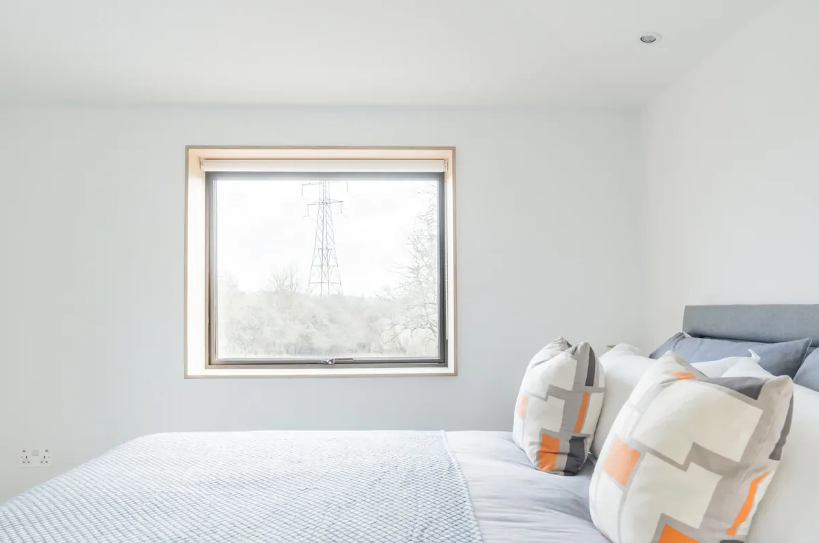 Minimal bedroom with white walls and grey bedding