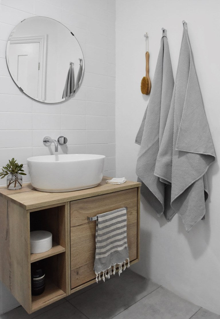 Bathroom corner with white tiles and wooden vanity unit. Grey towels and accessories