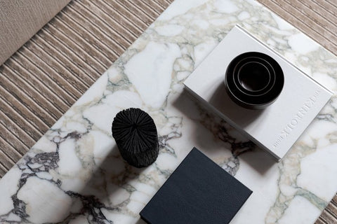 Marble table with magazine and black ceramics