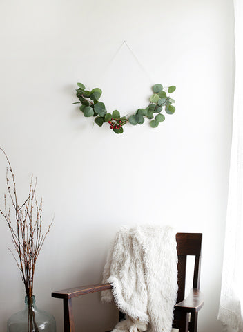 Minimal wreath hanging above wooden chair
