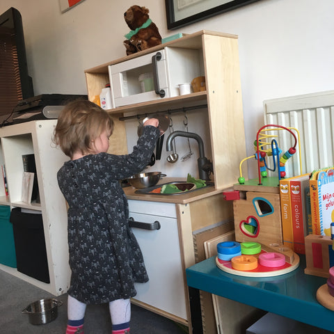 Toddler playing with wooden kitchen
