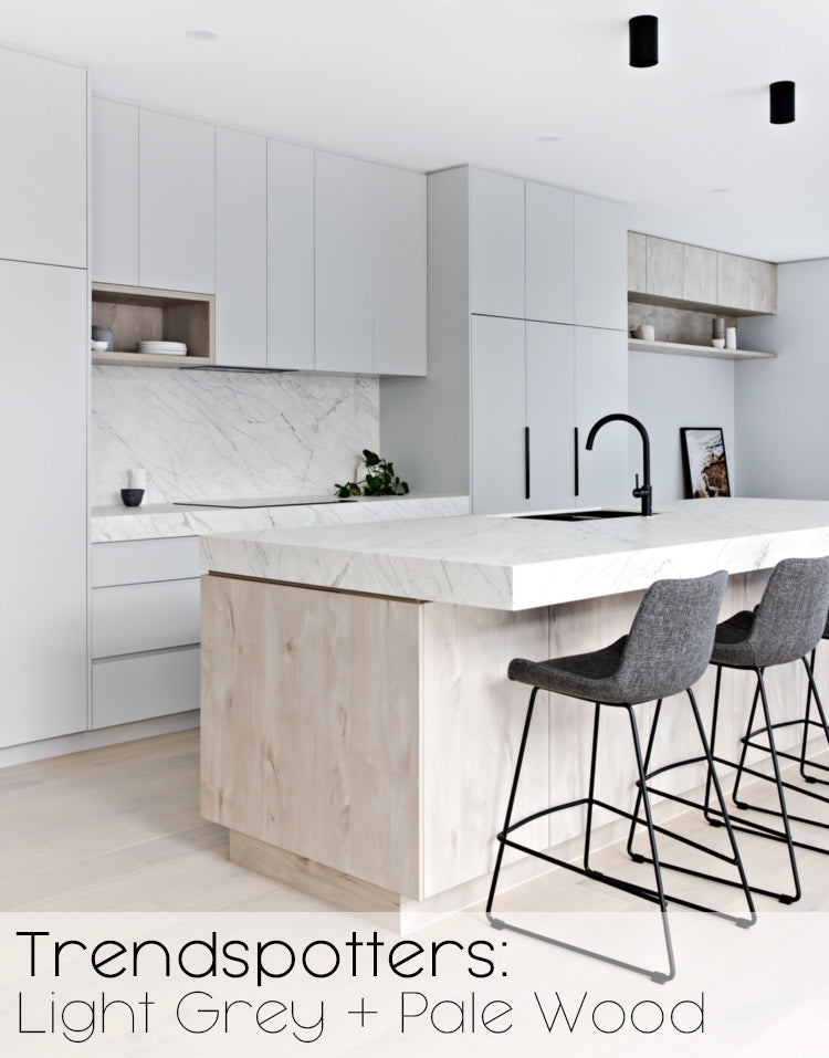 """Image of modern kitchen in pale grey with light wood island and grey chairs. Text reads """"Trendspotters: Light Grey + Pale Wood"""""""