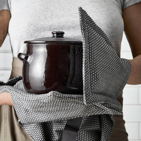 Holding cooking pot with grey oven gloves
