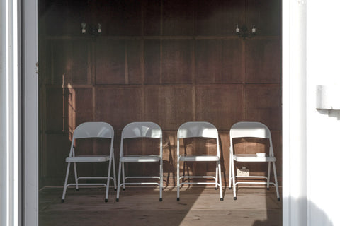 Panelled wooden wall with a row of white folding chairs