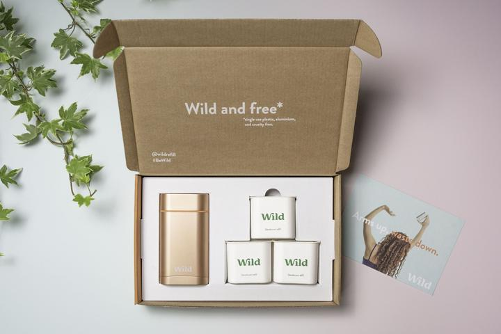 Box of Wild deodorant with applicator and refills, all in shades of gold