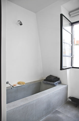 Build in concrete bath tub with towels and sponge